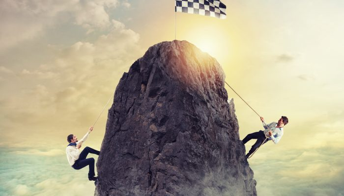 image depicting two businessmen competing to reach the same summit