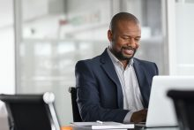photo of black mature businessman working on laptop